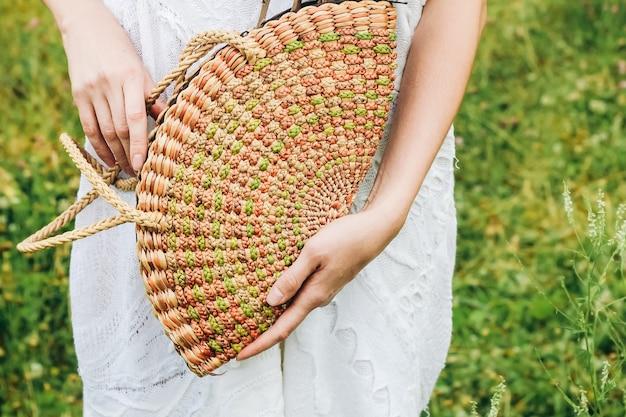 Nas mãos de uma garota, uma bolsa da moda de vime ecológica.