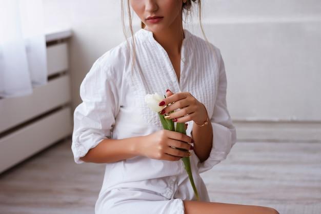 Nas mãos de uma garota uma tulipa. foto macia. publicidade de cosméticos