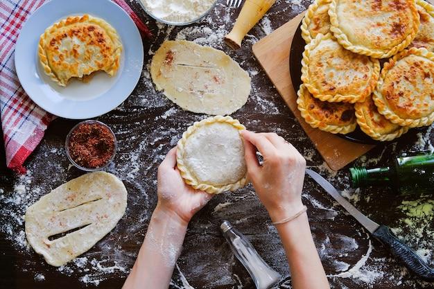 Nas mãos do cozinheiro georgiano pão de massa crua. uma mulher faz um bolo ou khachapuri.