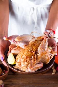 Nas mãos femininas o frango em molho e temperos em um prato