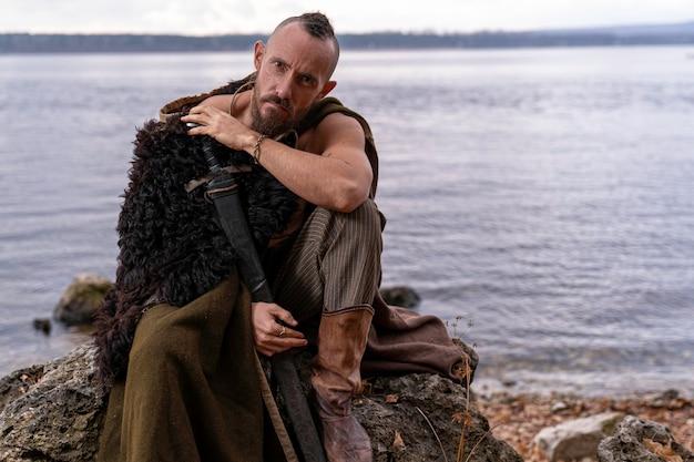 Nas margens do rio, um viking vestido com uma pele de animal está sentado em uma pedra segurando uma espada embainhada