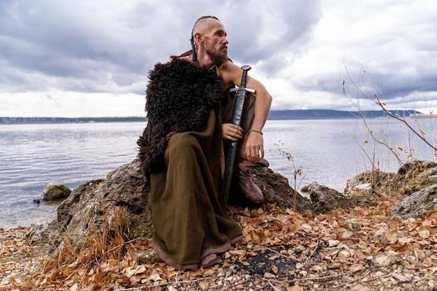 Nas margens do rio, um viking vestido com uma pele de animal está sentado em uma pedra segurando uma espada