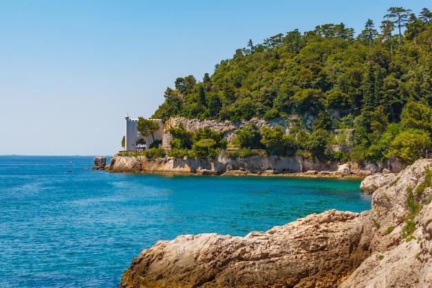 Nas montanhas rochosas é um castelo acima de uma água azul do mar. na área distante é o castelo nas montanhas com fendas sobre a clareira do mar.