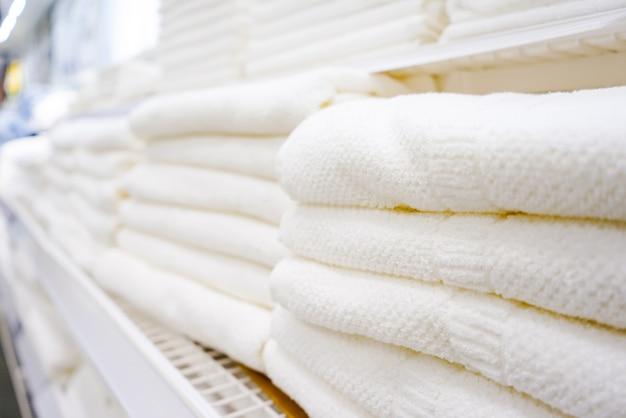 Nas prateleiras da loja há muitas toalhas de banho brancas