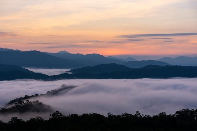 Nascer do sol acima sobre a grande montanha e névoa empilhadas superiores sobre a floresta.