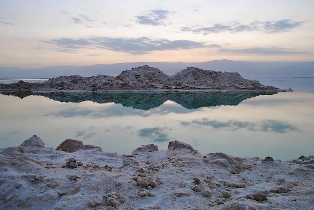 Nascer do sol ao longo da costa do mar morto em israel. o lugar mais baixo da terra. cristais de sal ao nascer do sol