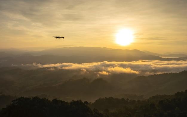 Nascer do sol bonito e silhuetas de montanha em camadas no início da manhã.