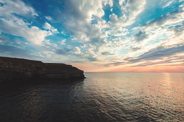 Nascer do sol brilhante da praia do destino das férias e penhascos do mar