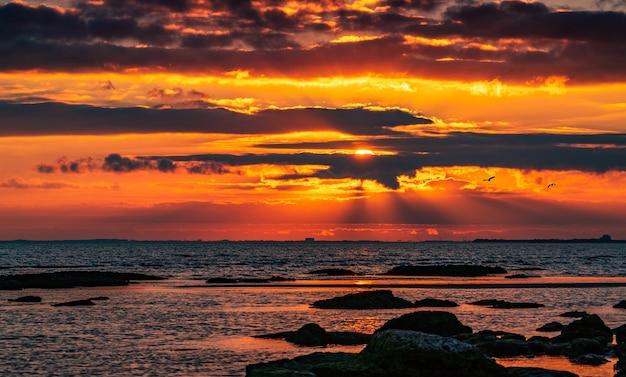 Nascer do sol colorido na costa rochosa