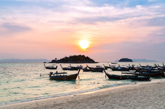 Nascer do sol da manhã muitos barcos longtail de madeira estacionando no mar azul ao nascer do sol praia vista para o mar tranquilo
