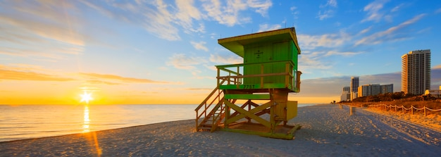 Nascer do sol de miami south beach com torre de salva-vidas e litoral com nuvens coloridas e céu azul.
