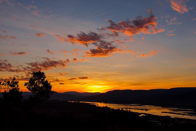 Nascer do sol dourado sobre o rio kong e montanha