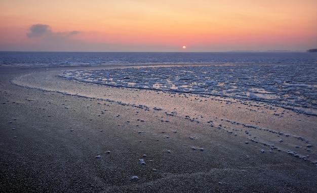 Nascer do sol e mar congelado. bela paisagem de inverno com lago no período da manhã. aurora