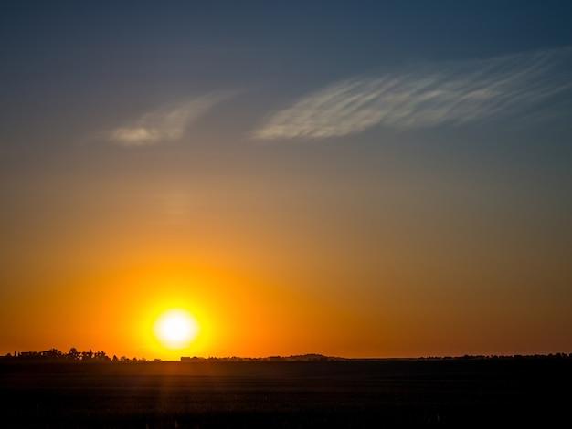 Nascer do sol em campo. campo pela manhã. céu dramático durante o nascer do sol_