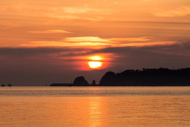 Nascer do sol entre a ilha e as nuvens