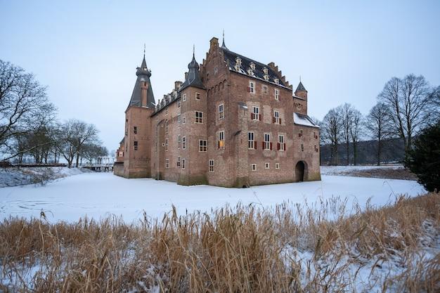 Nascer do sol hipnotizante sobre o castelo histórico de doorwerth durante o inverno na holanda