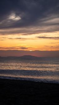 Nascer do sol incrível na praia tropical. sol amarelo sobre o mar. ondas de cores laranja. fundo da natureza. bela cena serena. manhã. a luz do sol reflete na superfície da água