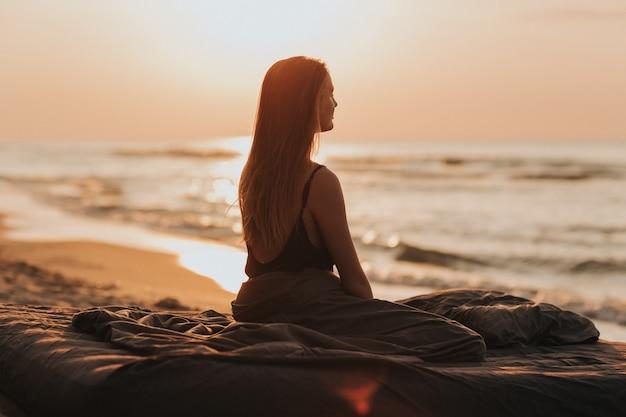 Nascer do sol lindo da manhã no mar, silhueta da menina no por do sol. mulher relaxa à beira-mar. conceito de meditação