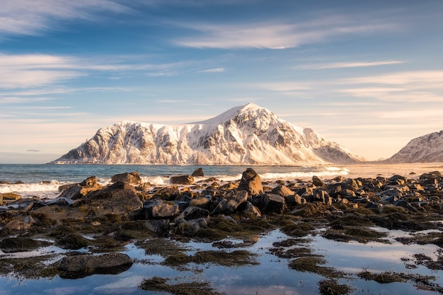 Nascer do sol na montanha de neve no litoral na praia de skagsanden