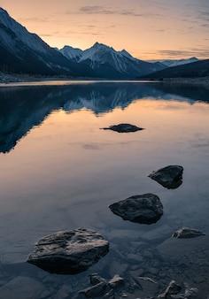 Nascer do sol na montanha rochosa com pedras no lago medicine no parque nacional de jasper