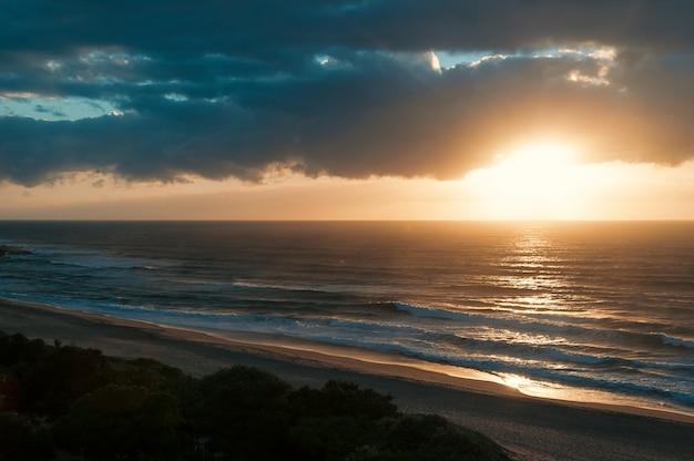 Nascer do sol na praia do oceano, vista do mar, com nuvens dramáticas no horizonte