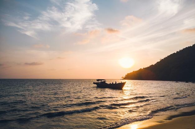 Nascer do sol na praia tropical de koh rong camboja, paisagem com barcos longtail, enquanto o sol está subindo. koh kong sanloem