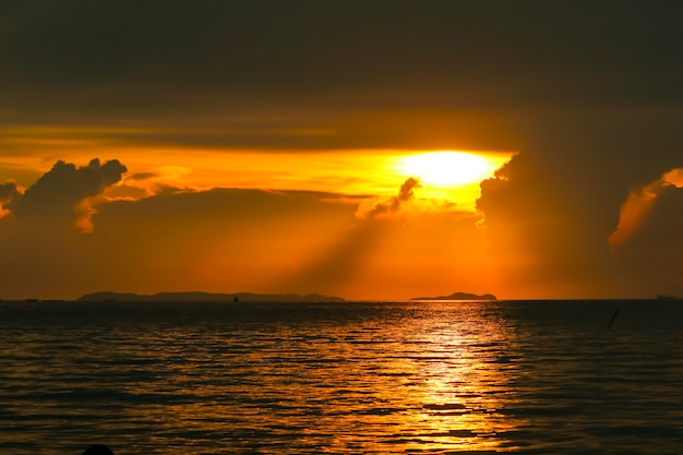 Nascer do sol na silhueta barco de pesca do céu nuvem e na ilha do mar