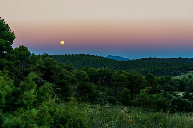 Nascer do sol no parque natural sierra de mariola com lua cheia, banyeres de mariola, comunidade valenciana, espanha.