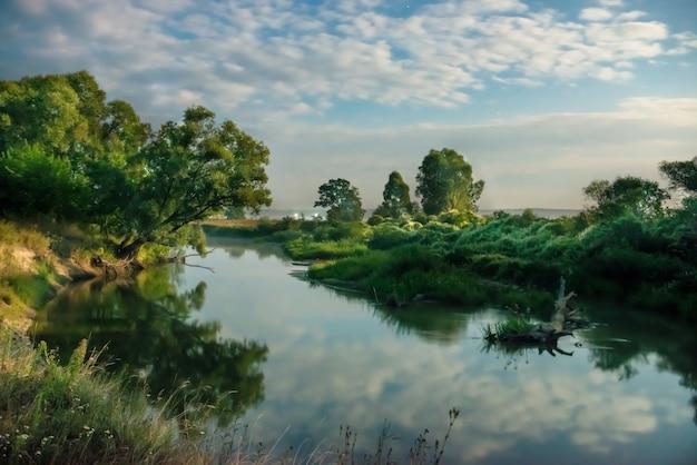 Nascer do sol no rio com nuvens acima da água
