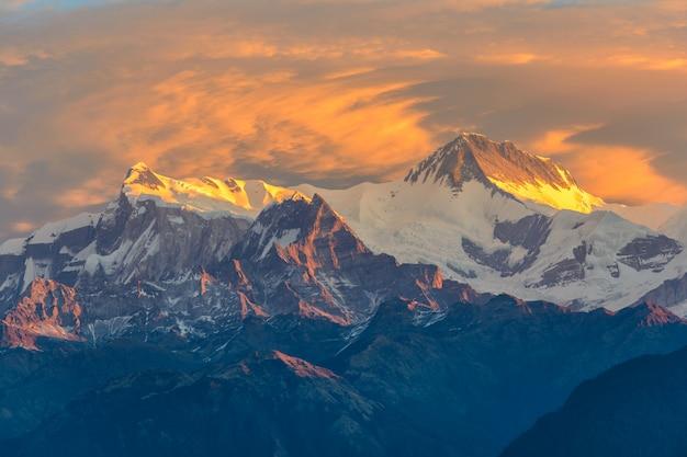 Nascer do sol nublado bonito nas montanhas com cume de neve