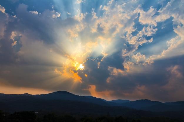Nascer do sol ou por do sol bonito com nuvens e raio de sol dourado sobre montanhas.