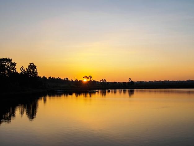 Nascer do sol perto da lagoa na montanha na tailândia, imagem de silhuetas