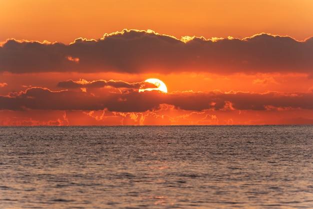 Nascer do sol, pôr do sol no horizonte do mar e nuvens laranja