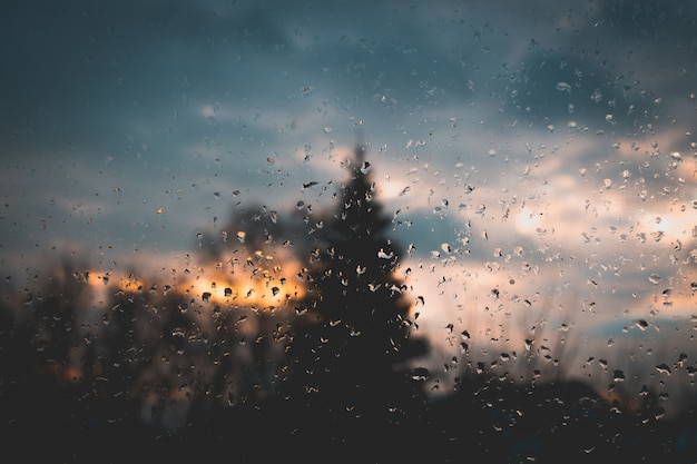 Nascer do sol por trás da janela molhada