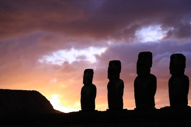 Nascer do sol roxo céu nublado sobre a silhueta de estátuas moai