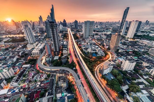 Nascer do sol sobre a estrada trident em sathorn, a ponte taksin e o tráfego iluminado em bangkok, tailândia