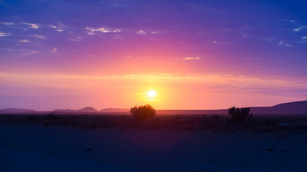 Nascer do sol sobre o deserto de namib, no parque nacional maravilhoso de namib naukluft, destino do curso em namíbia, áfrica.