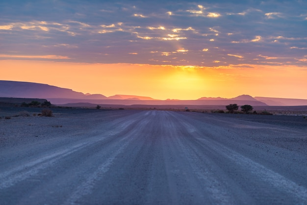 Nascer do sol sobre o deserto de namib, roadtrip no parque nacional maravilhoso de namib naukluft, destino do curso em namíbia, áfrica. luz da manhã, névoa e nevoeiro, aventura fora da estrada.