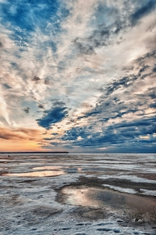 Nascer do sol sobre o gelo do rio na manhã de inverno, à distância pescadores sentados