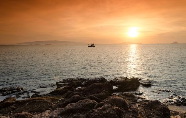 Nascer do sol sobre o mar e barco de pesca na zona rural, hua hin-tailândia