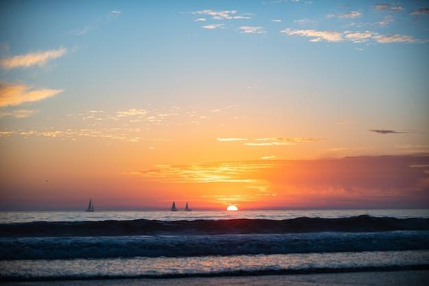 Nascer do sol sobre o mar e uma bela paisagem de nuvens. pôr do sol da praia do oceano colorido.