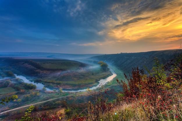 Nascer do sol sobre um pequeno rio enevoado