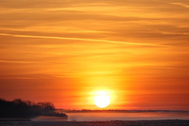 Nascer do sol sobre um prado com nevoeiro. início da primavera.