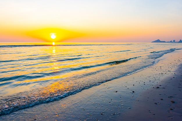 Nascer ou pôr do sol com céu crepuscular e praia do mar