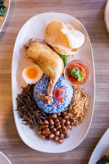 Nasi lemak é um arroz malaio cozido em leite de coco servido com frango frito.