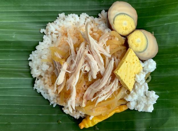 Nasi liwet solo, um alimento tradicional de surakarta, indonésia, saboroso arroz cozido no vapor com curry de frango desfiado e ovo de galinha