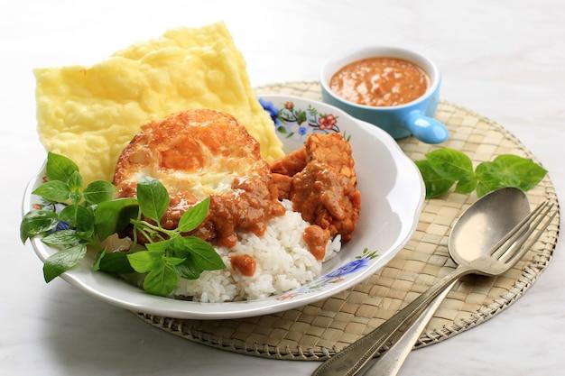 Nasi pecel madiun com ovo e tempeh frito. pecel é um molho picante de amendoim, tipicamente do leste de java