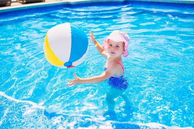 Natação, férias de verão - linda garota sorridente no chapéu-de-rosa e maiô azul, jogando na água azul com bola multicolor inflável em uma piscina