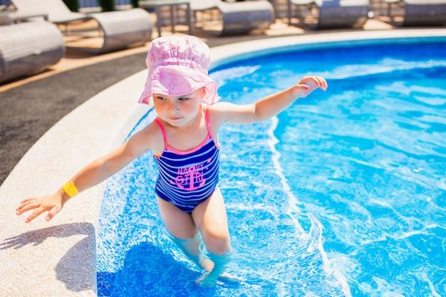 Natação, férias de verão - linda garota sorridente no chapéu-de-rosa e maiô azul, jogando na água azul em uma piscina.