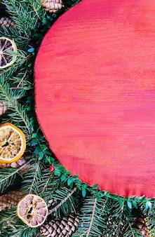 Natal, ano novo, composição vertical do feriado de inverno com superfície de madeira vermelha em galhos de árvore verde do abeto, fatias de laranja secas, cones e laço vermelho.